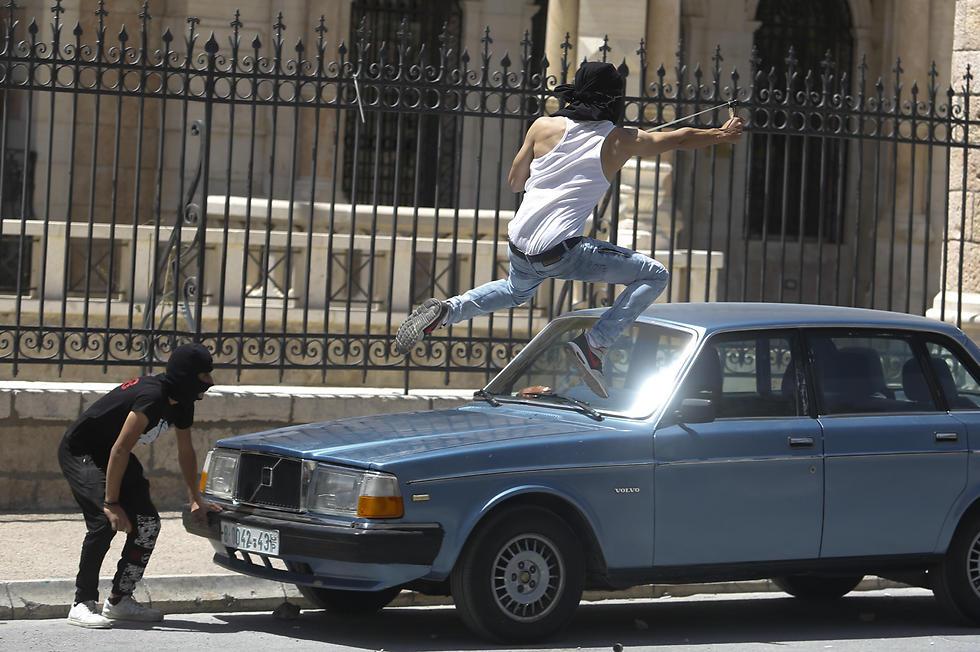 """פלסטינים מתעמתים עם כוחות הביטחון הישראליים ביום העצמאות, """"יום הנכבה"""" מבחינתם (צילום: AP) (צילום: AP)"""