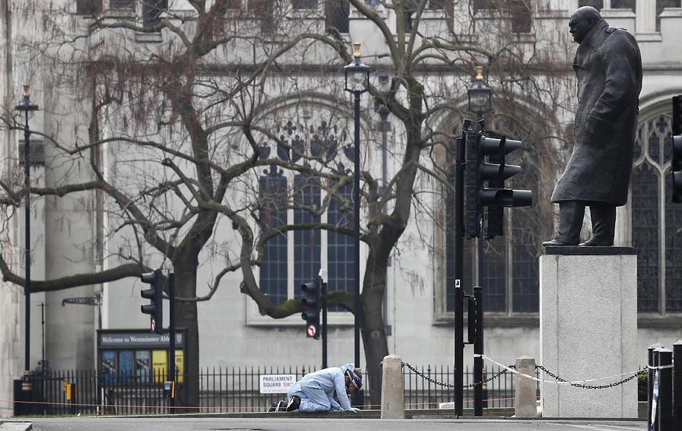 חוקר זיהוי פלילי מחפש ראיות למרגלות פסל צ'רצ'יל ליד הפרלמנט בלונדון, אחרי פיגוע הדריסה והדקירות שם (צילום: AP) (צילום: AP)