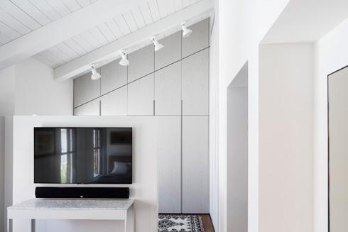 קיר הטלוויזיה מול המיטה, ומאחוריו חדר ארונות פתוח  (צילום: עמית גרון)