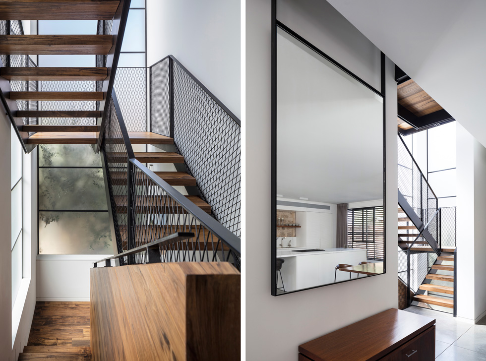 גרם מדרגות קל, עשוי מדרכי עץ אגוז, מעקות ברזל ורשת שחורה, כלוא בין שני קירות המנותקים, כביכול, מהבית (צילום: עמית גרון)