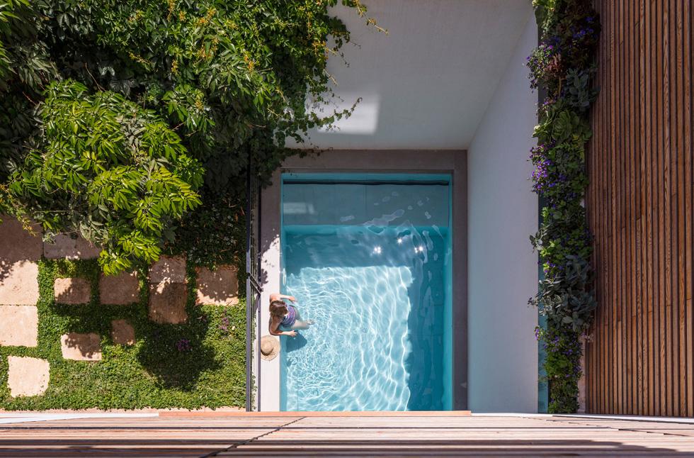 מבט מהמרפסת אל בריכת השחייה הקטנה בחצר האחורית. כיוון שהקומות העליונות גדולות מקומת המרתף, הבריכה נראית כאילו היא נכנסת לבית (צילום: עמית גרון)