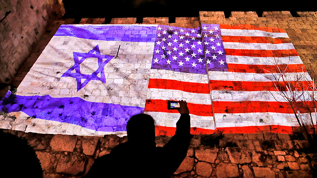 US and Israel flags on the Old City walls  (Photo: AFP)