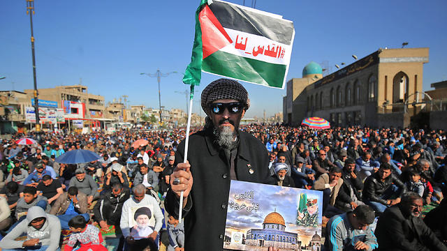 A protester in Iraq holding a picture of the Al-Aqsa Mosque and a Palestinian flag with the caption '#Jerusalem is ours' (Photo: AFP)