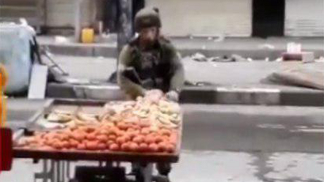 The squad commander takes fruit from the stand
