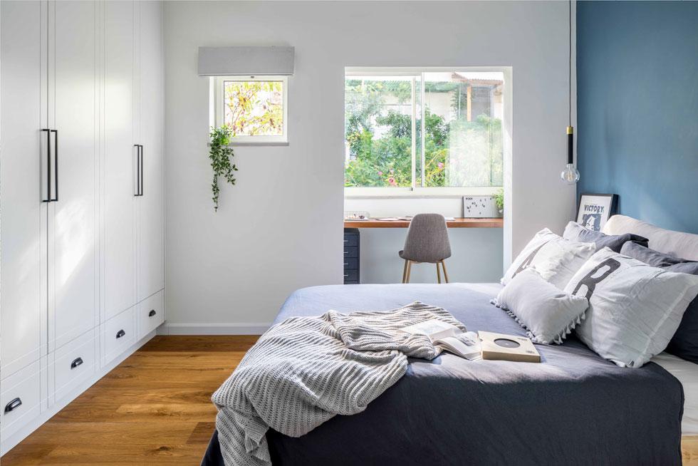 חדר השינה קטן ויעיל, ובמרפסת הצמודה אליו יש פינת עבודה מוארת, הפונה אל הרחוב השקט. כיסוי שגולש עד הרצפה עוטף את המיטה הפשוטה  (צילום: יואב פלד)