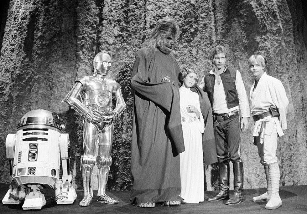 """""""מלחמת הכוכבים"""" היא גם מותג אופנתי, שרבים שומרים לו נאמנות. מארק האמיל בתפקיד לוק סקייווקר, הריסון פורד בתפקיד האן סולו וקארי פישר בתפקיד הנסיכה ליאה, יחד עם הדמויות צ'ובאקה, C-3PO ו-R2-D2 (צילום: AP)"""