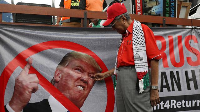 Malaysia's ex-PM Mahathir Mohamad poking Trump's eye (Photo: Reuters)
