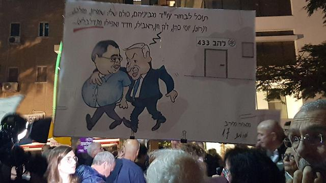 A sign at the protest showing PM Netanyahu and MK David Bitan, with the former saying: 'You can pick a laywer from among them, they're all mine: Shimron, Molcho, Weinroth, Yossi Cohen, Jacques Chen, Rabello, Hadad and even Mandelblit...'