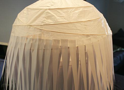 באמצע הדרך, משולשי הנייר מודבקים קומה קומה על אהיל הנייר העגול (צילום: נעם רוזנברג)