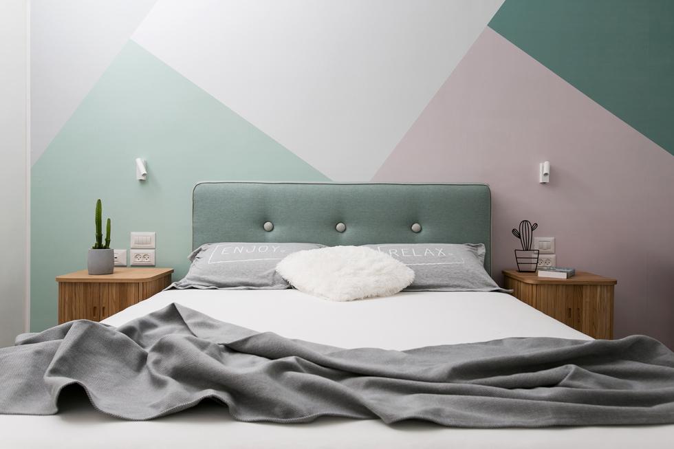 חדר השינה החדש של בני הזוג. על הקיר בגב המיטה הודבק קנבס מודפס, בדוגמה גיאומטרית שהמעצבת יצרה. היא הציגה לבני הזוג כמה אפשרויות בהדמיה של החדר, כדי שייקל עליהם לבחור (צילום: שירן כרמל)