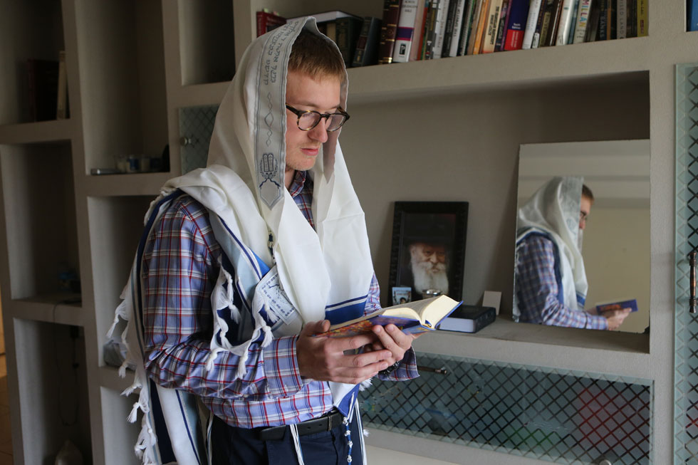 קולסון בדירה הירושלמית שבה הוא גר עם ערבי תומך ישראל והומו חרדי שיצא בשאלה. למטה: היכרות עם מכון פרדס, שבו הוא לומד יהדות (צילום: אלכס קולומויסקי)