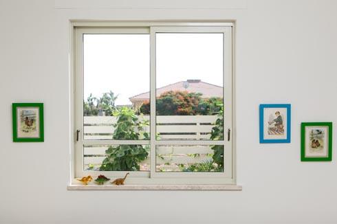 החלון באחד מחדרי הילדים צופה אל החצר (צילום: שירן כרמל)