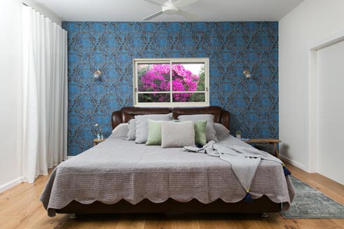 חדר השינה של בעלי הבית. פריחת הבוגונוויליה בחלון  (צילום: שירן כרמל)