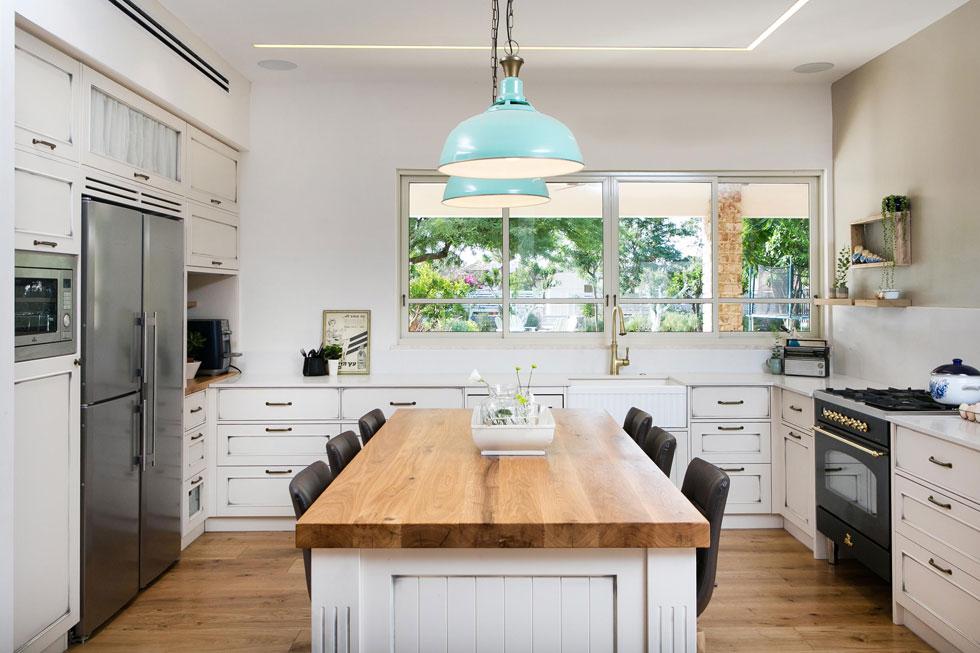 המטבח בנוי בצורת האות ח', פונה בחלונות גדולים לחצר, ובמרכזו אי מוקף בכסאות מרופדים (צילום: שירן כרמל)