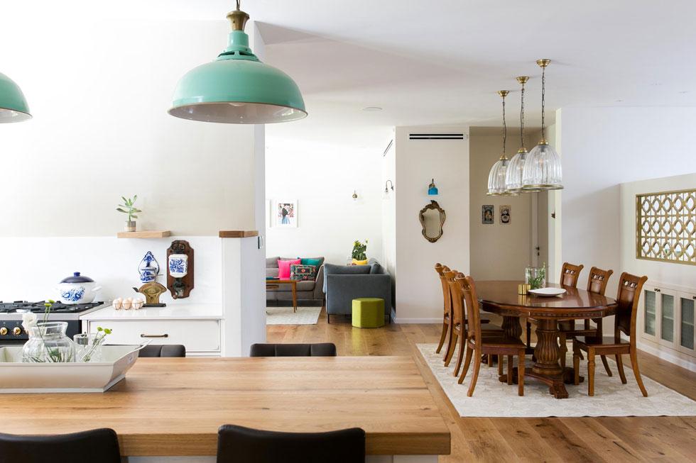 שולחן האוכל העתיק מעץ היה בבית המשפחה גם לפני השיפוץ. מאחוריו מפריד מפינת המשפחה קיר נמוך שבו שולבה משרבייה אוורירית (צילום: שירן כרמל)