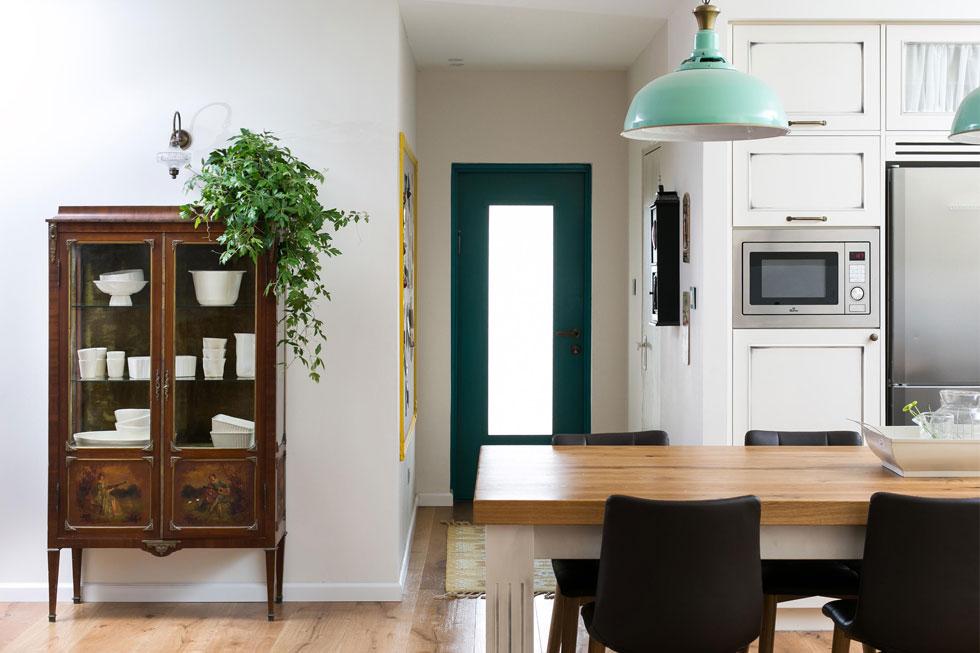"""מאחורי המטבח יש ממ""""ד המשמש כחדר עבודה. דלת הטורקיז לצדו מובילה לחניה. ארון הוויטרינה הובא מבית אמה של בעלת הבית (צילום: שירן כרמל)"""
