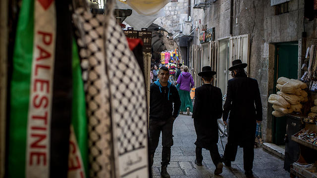 Jewish men pass a store selling Palestinian clothing in the Muslim Quarter of the Old City (Photo: Getty Images)