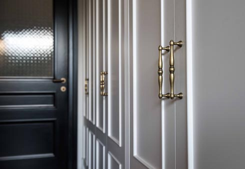 קיר הארונות הלבנים בדרך לחדר השינה. דלתות הפנים שחורות ומשולבת בהן זכוכית   (צילום: גלעד רדט)