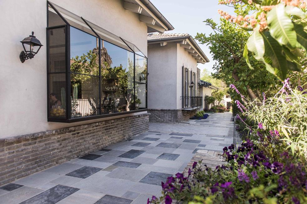 הכניסה אל הבית החדש שקועה בין שני חלקיו, ומסומנת באמצעות ''שטיח'' של אריחים. את הכפריות מאזנים אלמנטים תעשייתיים, כמו פרופילי הברזל של החלונות וויטרינת המטבח החורגת מהקיר אל השביל ההיקפי (צילום: גלעד רדט)