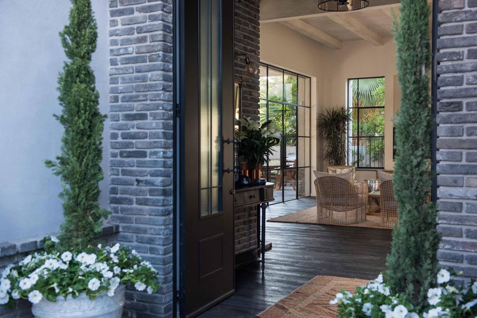 דלת הכניסה השחורה נפתחת אל הסלון. הפרקט החום והתקרה השטוחה, שקורות העץ בולטות בה, מבססים את האופי הכפרי של הבית (צילום: גלעד רדט)