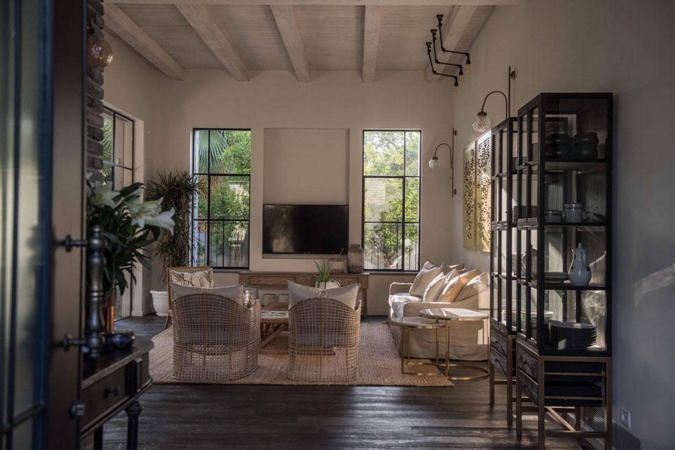 הסלון בהיר וקליל, עם רהיטי קש ועץ ושטיח חבל. ויטרינות זכוכית גדולות מאפשרות יציאה אל הגינה האחורית (צילום: גלעד רדט)