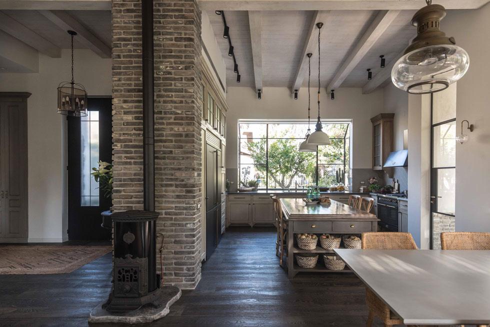 המטבח בנוי בצורת האות ח', ומוסתר מאחורי קיר המבואה, שכוסה בלבנים אפורות. בדופן הקיר, במרכז החלל, קמין ברזל (צילום: גלעד רדט)