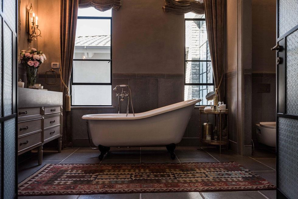בעלת הבית ביקשה לשלב בחדר הרחצה אלמנטים רומנטיים. האמבטיה עומדת על רגליים מעוטרות, והקירות חופו בחלקם התחתון באבן (צילום: גלעד רדט)