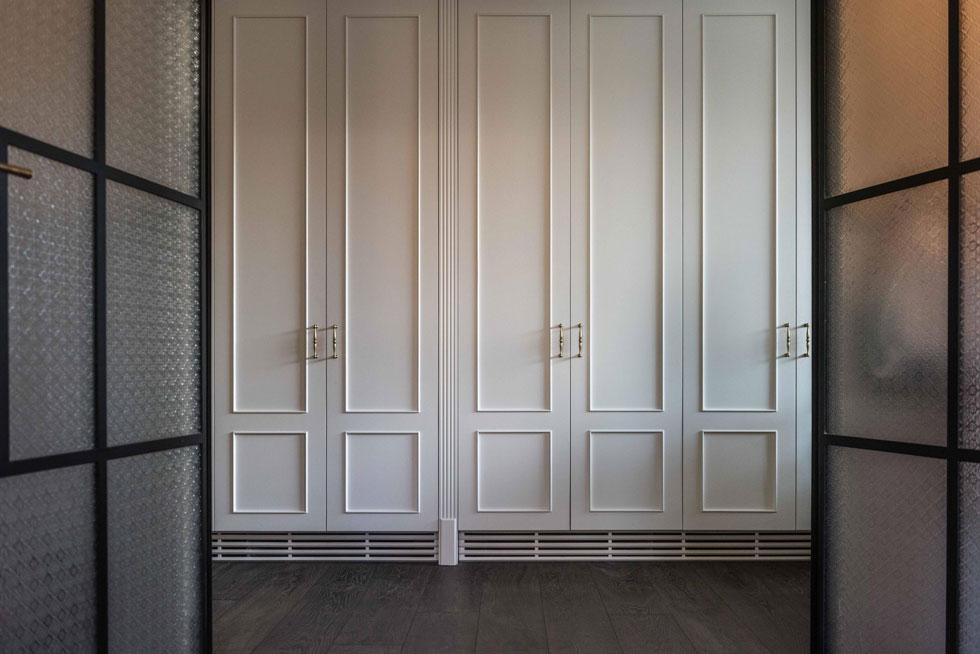 מבט דרך דלתות הזכוכית והברזל של חדר הרחצה אל המסדרון. לאורכו נבנו ארונות עם דלתות ממוסגרות (צילום: גלעד רדט)
