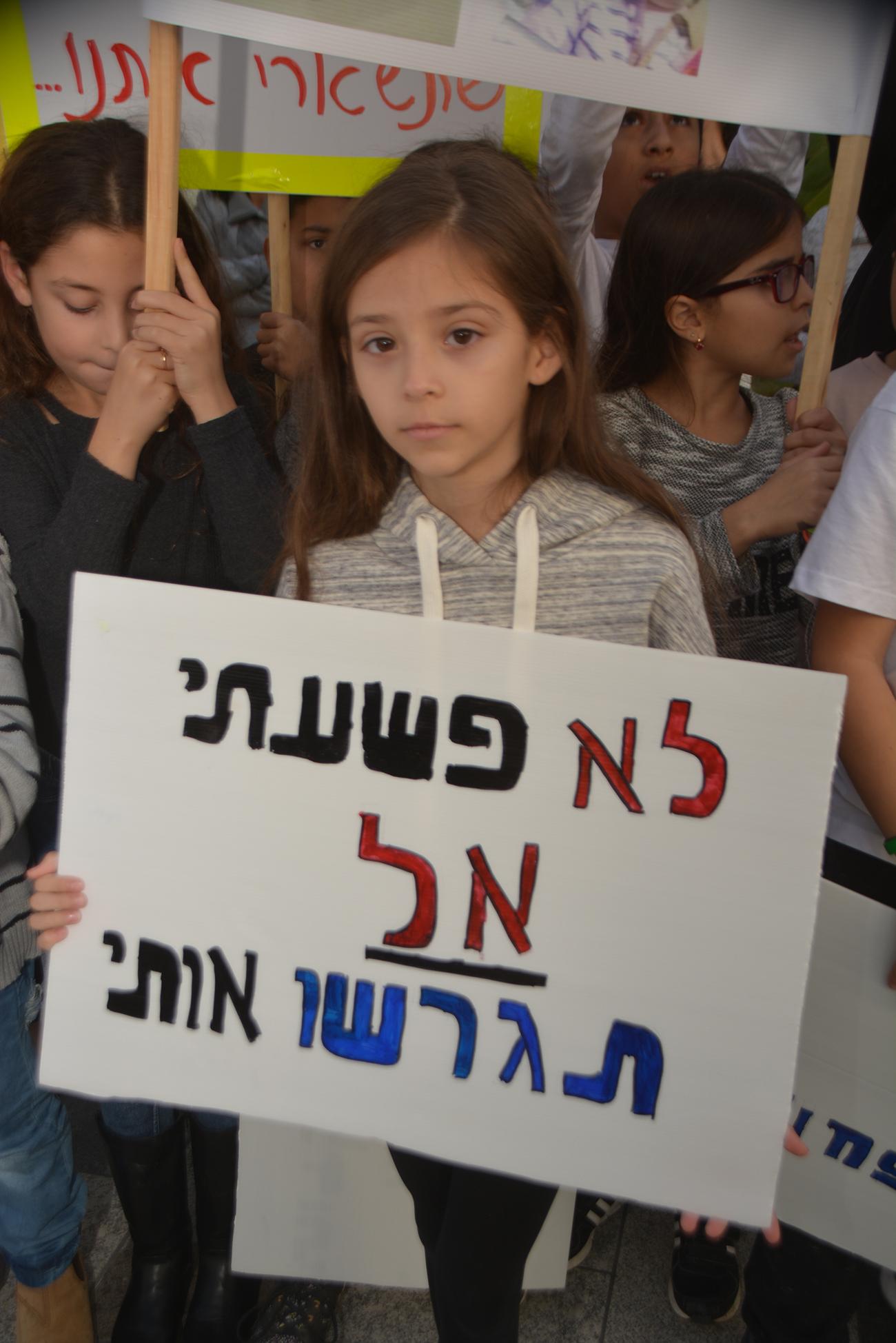 "Лаура с плакатом: ""Я не преступник - не высылайте меня"". Фото: Меир Охайон"