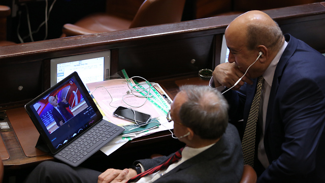 MKs Nachman Shai and Zouheir Bahloul watching TV satire show Eretz Nehederet during discussions on the bill in the Knesset (Photo: Alex Kolomoisky)