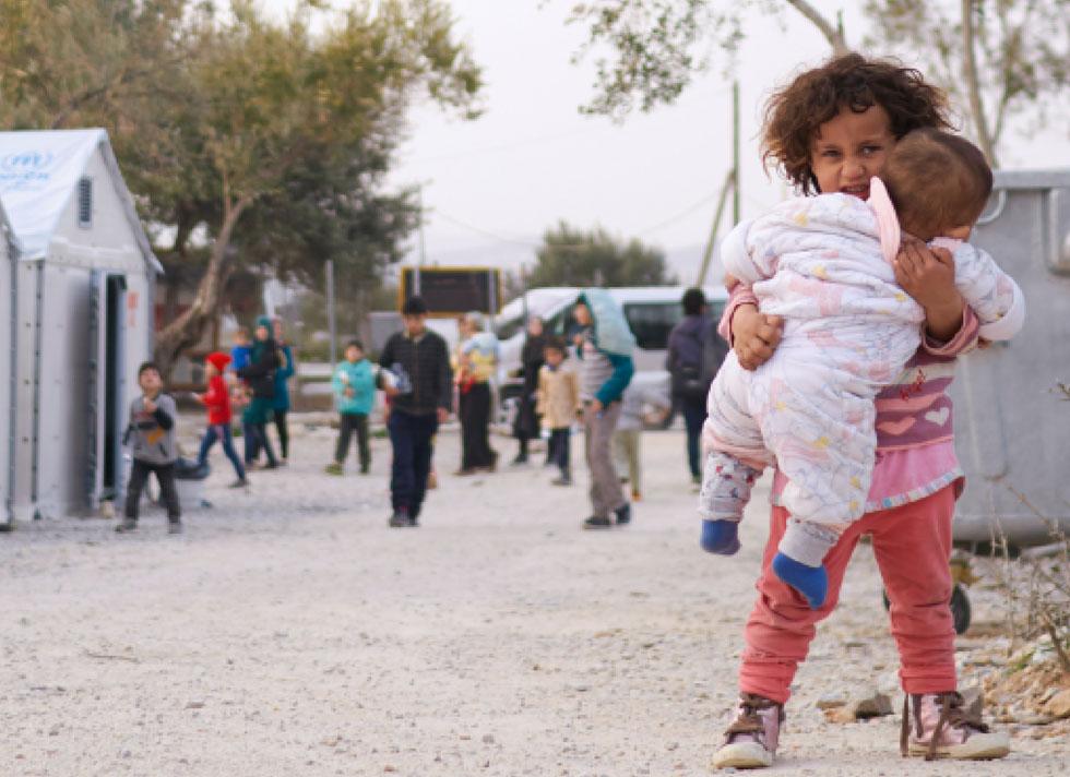 פליטים על רקע Better Shelter  של איקאה. לאחרונה דווח שהשימוש במבנים הזמניים של איקאה הוקפא בגלל חשש מסכנת התלקחות, מה שמעמיד כיום את המיזם כולו בסימן שאלה גדול (צילום: באדיבות איקאה)