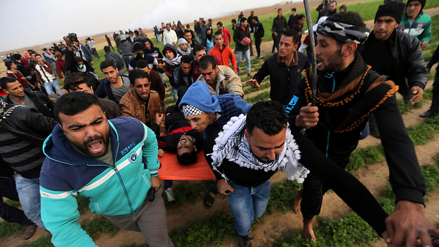 Evacuating wounded Palstinians on Gaza border (Photo: Reuters)