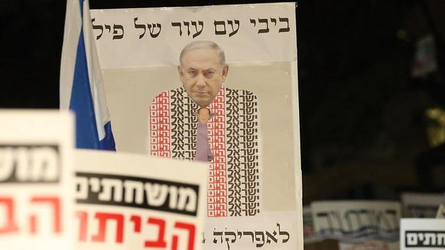 PM draped in the ostensibly pro-Netanyahu newspaper Israel Hayom (Photo: Moti Kimchi)