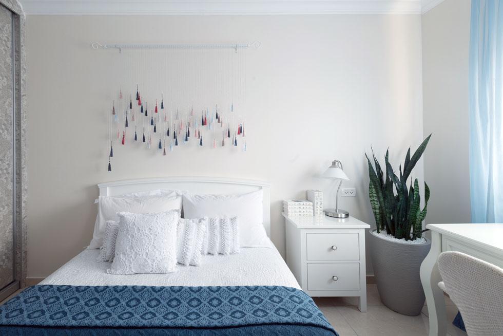 חדר השינה של סבתא אלה. מעל המיטה נתלה מובייל טקסטיל שיצרו המעצבות. השולחן הלבן והווילונות הבהירים יוצרים אווירה רומנטית (צילום: גדעון לוין 181 מעלות)