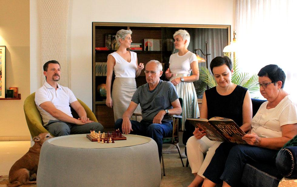"""משפחת בלאוסוב-קוזלוב בסלון דירתם החדשה. יושבים מימין לשמאל: סבתא אלה, אמא נטשה, סבא ליאוניד, אבא אדי. מאחור עומדות המעצבות: הבת קסניה (מימין) וטופז רוזנברגר. """"למזלנו, בניגוד להרבה משפחות אחרות"""", אומרת נטשה, """"למדנו לחיות ביחד, והסידור הזה עובד לנו טוב"""" (צילום: Designstudio.be)"""