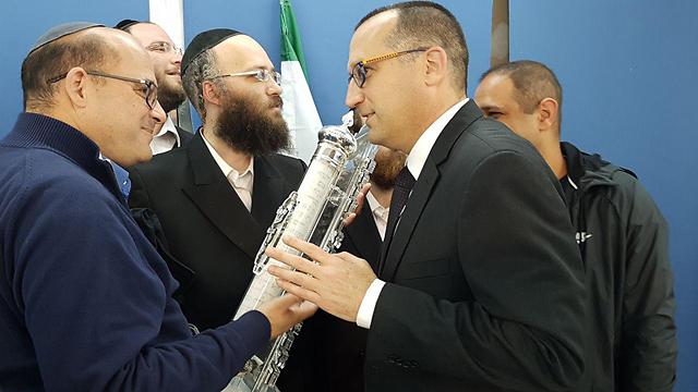Mayor Kunik kissing a mezuzah after the vote