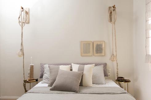 שולחנות צד שרגליהם קוצרו ליד המיטה, ומעל תלויות מנורות עם אהילי בד של סטודיו ''בילונגינג'' (צילום: שירן כרמל)