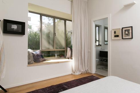 וילונות לבנים מרככים את החלון הגדול (צילום: שירן כרמל)