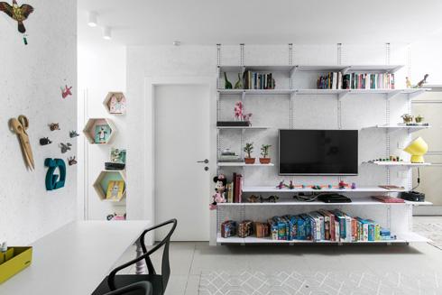 על הקיר מערכת של מדפים משרדיים פשוטים (צילום: שירן כרמל)