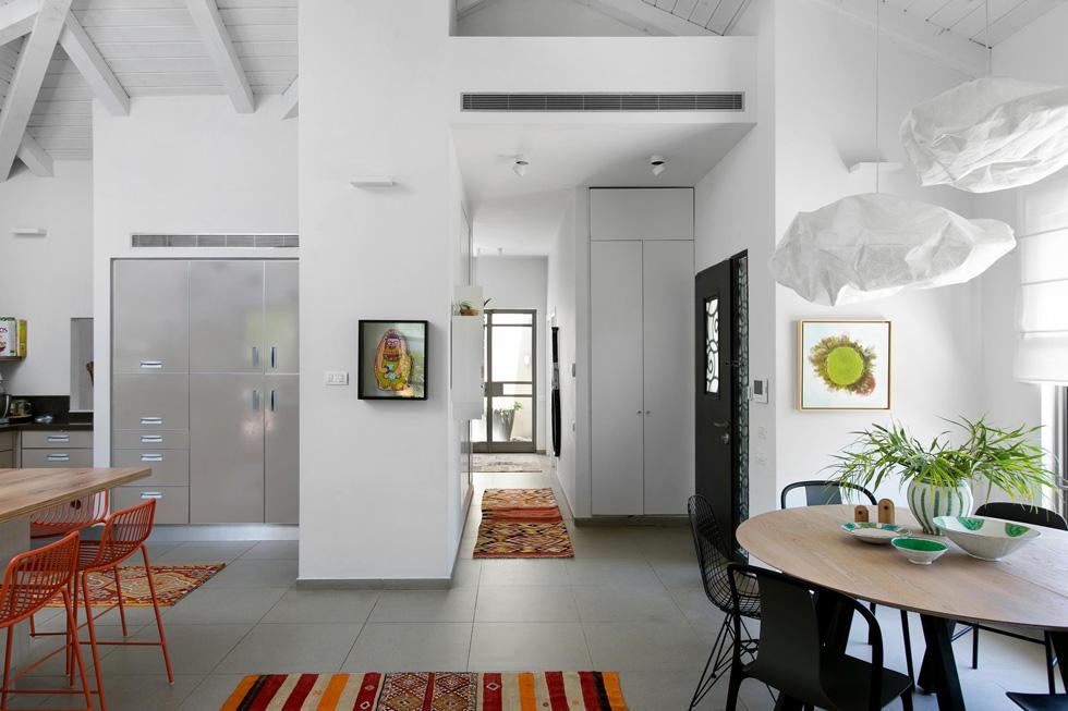 מבט מהסלון אל הכניסה והמסדרון המוביל לחדרים. שטיחונים מכניסים צבע לרקע הבהיר. הקוף על הקיר הוא עבודה של האמנית קרן שפילשר  (צילום: שירן כרמל)