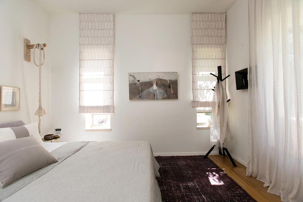 המיטה בחדר ההורים הוצבה על שטיח וינטג' סגול, בגוון האהוב על בעלת הבית. בין שני החלונות תלויה עבודה של טלי נבון (צילום: שירן כרמל)