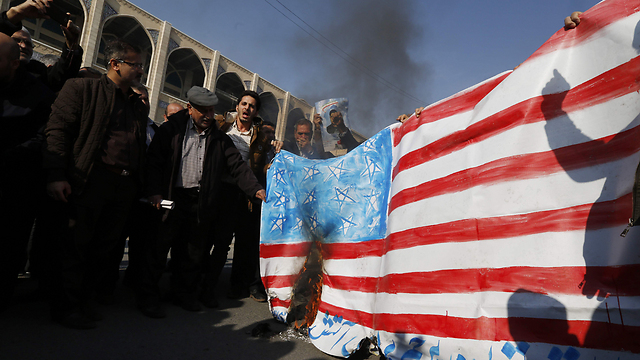 Iranian pro-government demonstrators burning a US flag, Friday (Photo: AFP)