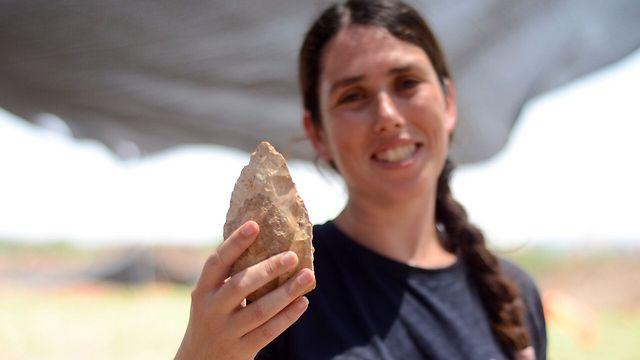 מעין שמר, מנהלת החפירה מטעם רשות העתיקות, מציגה אבן יד בת חצי מליון שנה (צילום: שמואל מגל, רשות העתיקות)