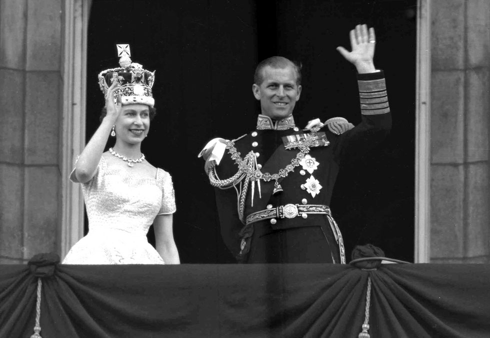 הכתר המלכותי והנפנוף שהפך לסימן ההיכר שלה. אליזבת השנייה עם הנסיך פיליפ (צילום: AP)