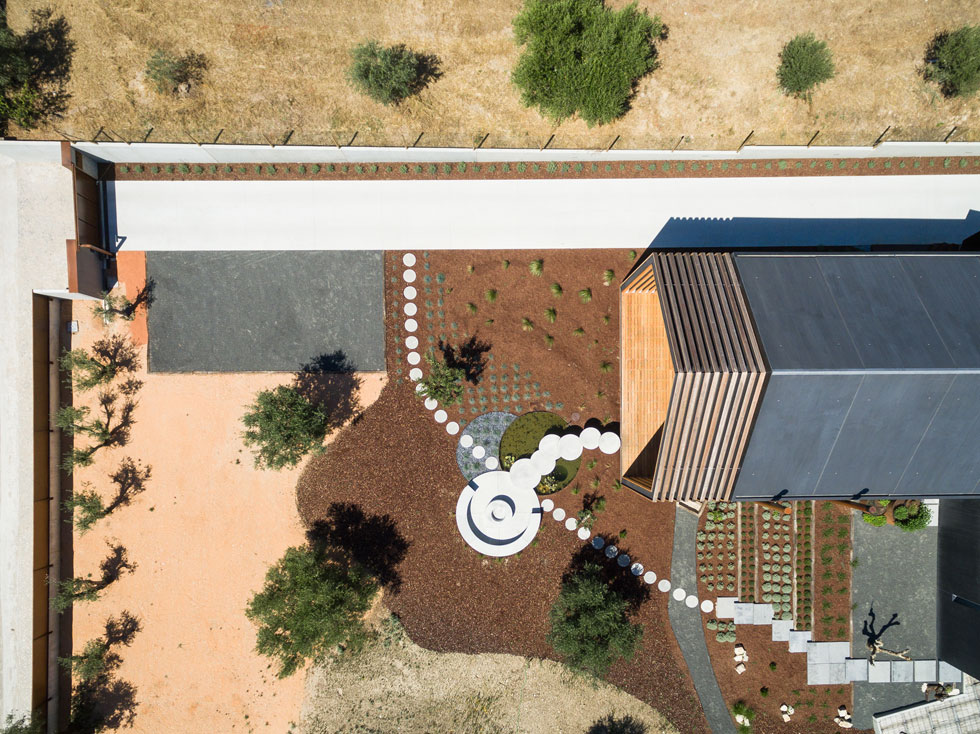 מבט מלמעלה. הצמחייה מקומית - עצי זית, ברושים, גינת ירק - ומרצפות בטון עגולות מובילות אל המרפסת הקדמית, המרחפת מעל הקרקע (צילום: Joao Morgado)