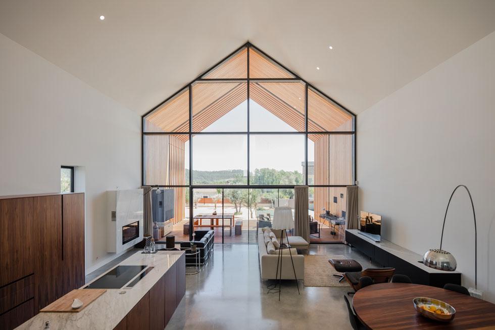 החלק המואר ביותר של הבית הוא מרחב הסלון והמטבח, שפתוח אל הנוף בקיר זכוכית עצום. מאחר ששלד הבית הוא גם המעטפת שלו, הפנים משוחרר מעמודים או קירות הנושאים את הגג. שתי פינות ישיבה מפנות גב זו אל זו - אחת פונה אל הקמין והשנייה אל המסך (צילום: Joao Morgado)