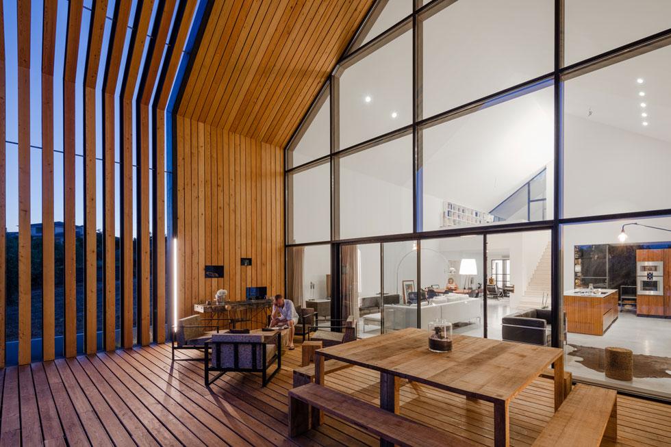 האדריכל במרפסת הסלון, שנעטפה בקורות עץ מרווחות, היוצרות מעין פרגולה עצומה (צילום: Joao Morgado)