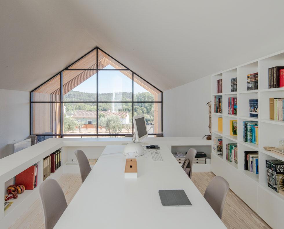 בגלריה למעלה חדר עבודה משפחתי ומזמין, עם שולחן גדול שסביבו יכולים לשבת ארבעת בני המשפחה (צילום: Joao Morgado)