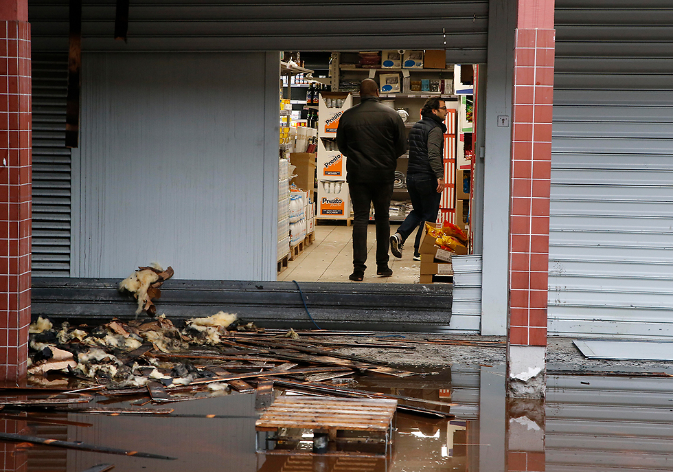 People walk in the kosher market after the fire (Photo: AP)