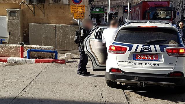 החשוד עולה לרכב השוטרים ()